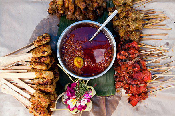 indonesian dish with satay chicken skewers - indonesia stock photos and pictures
