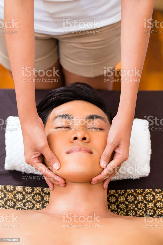 Indonesian man having wellness face massage royalty-free stock photo