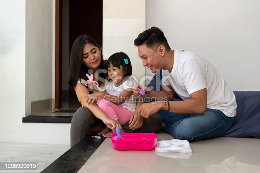 An Indonesian family of three, sitting on the floor, spending moments together, during the day, at home. The young daughter plays with plastic scissors, while parents hold other plastic toys, from a pink plastic box.