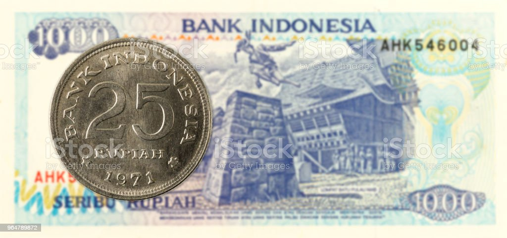 25 indonesian rupiah coin against 1000 indonesian rupiah bank note royalty-free stock photo
