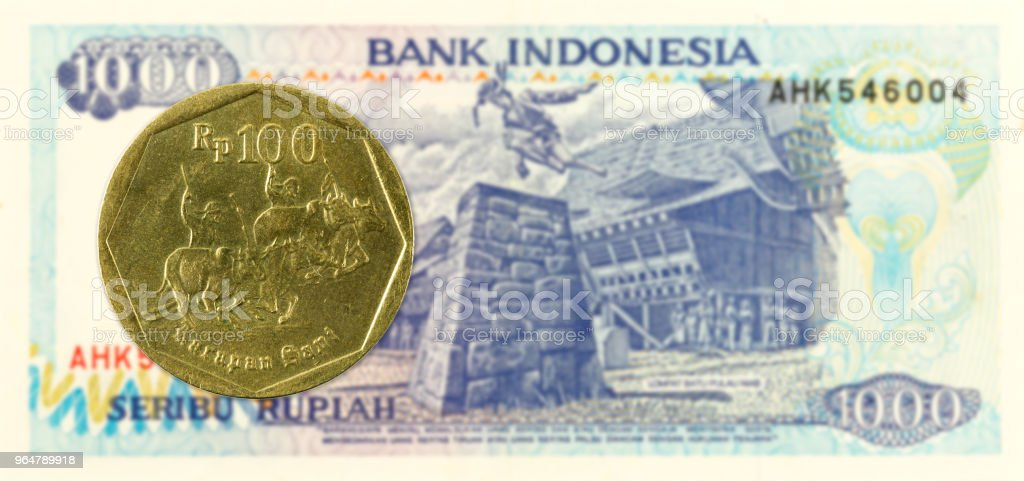 100 indonesian rupiah coin against 1000 indonesian rupiah bank note royalty-free stock photo