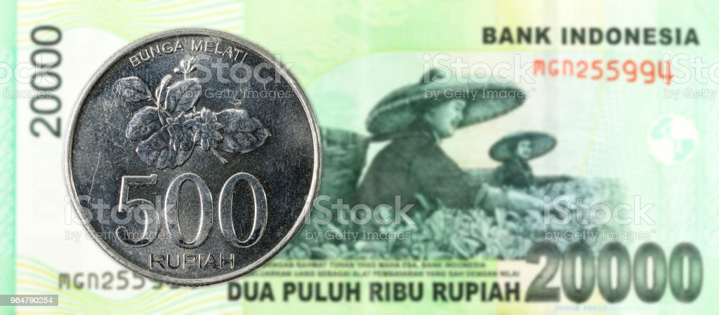 500 indonesian rupiah coin against 20000 indonesian rupiah bank note royalty-free stock photo