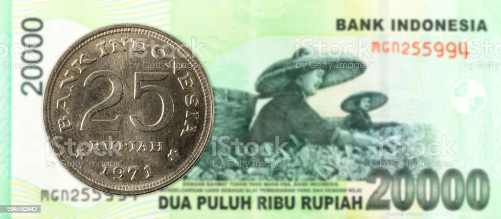 25 indonesian rupiah coin against 20000 indonesian rupiah bank note royalty-free stock photo