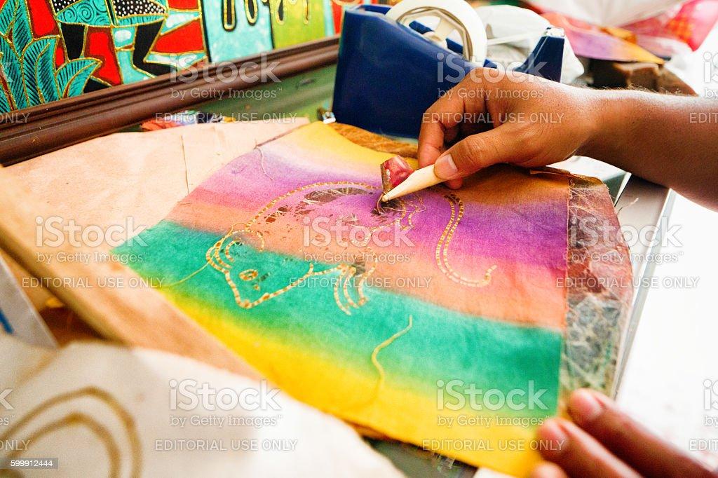 Indonesian street artist's hands making batik art stock photo