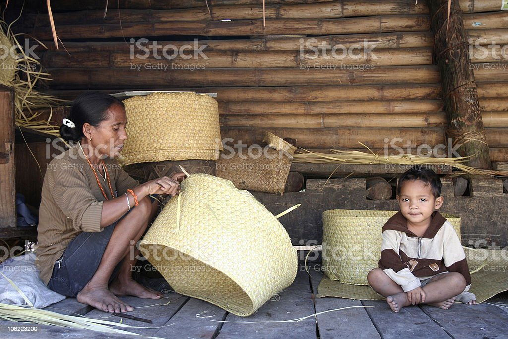 Indonesian Woman and Boy Weaving Baskets stock photo