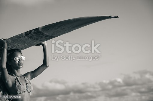 One woman, beautiful Indonesian woman holding a surfboard on the beach, black and white.