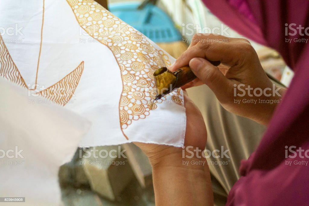 indonesian woman making batik design with wax stock photo
