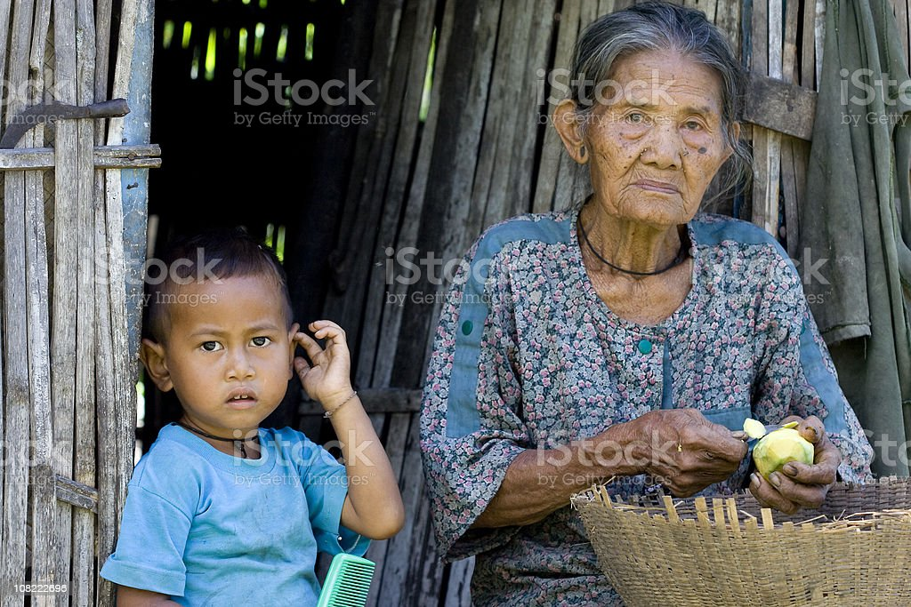 Indonesian Woman Peeling Fruit with Little Boy stock photo