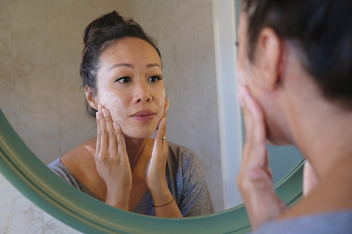Rear-view shot of a beautiful Indonesian woman washing her face using beauty cleanser soap. She's looking at her reflection in the mirror while thoroughly rubbing her face.