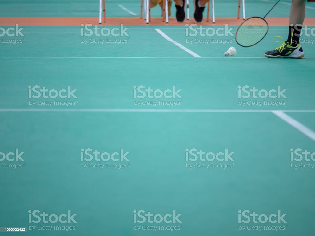 Cтоковое фото Indoor badminton court with the player leg , shuttle cock and the racquet, selective focus
