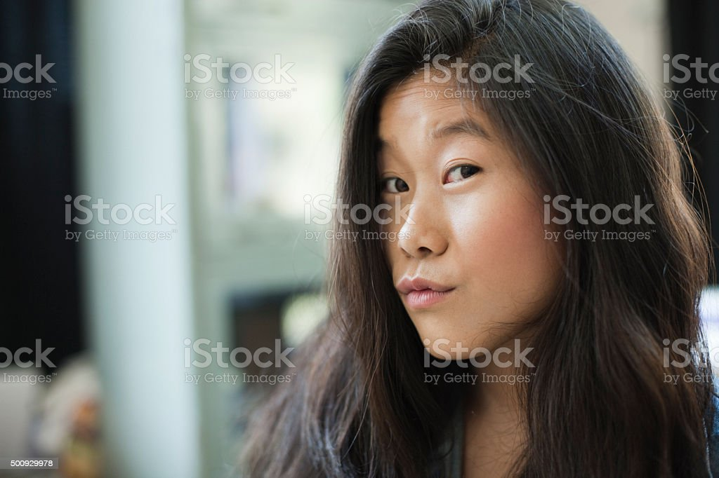 Indoor beautiful Asian girl looking at camera and pouting. stock photo