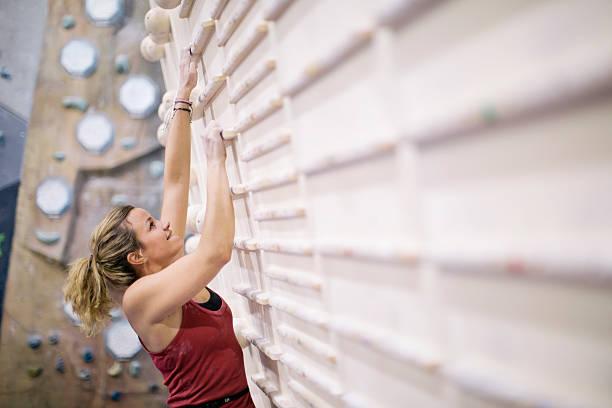 indoor-klettern in den bouldern fitnessstudio wand. - fitness herausforderung stock-fotos und bilder