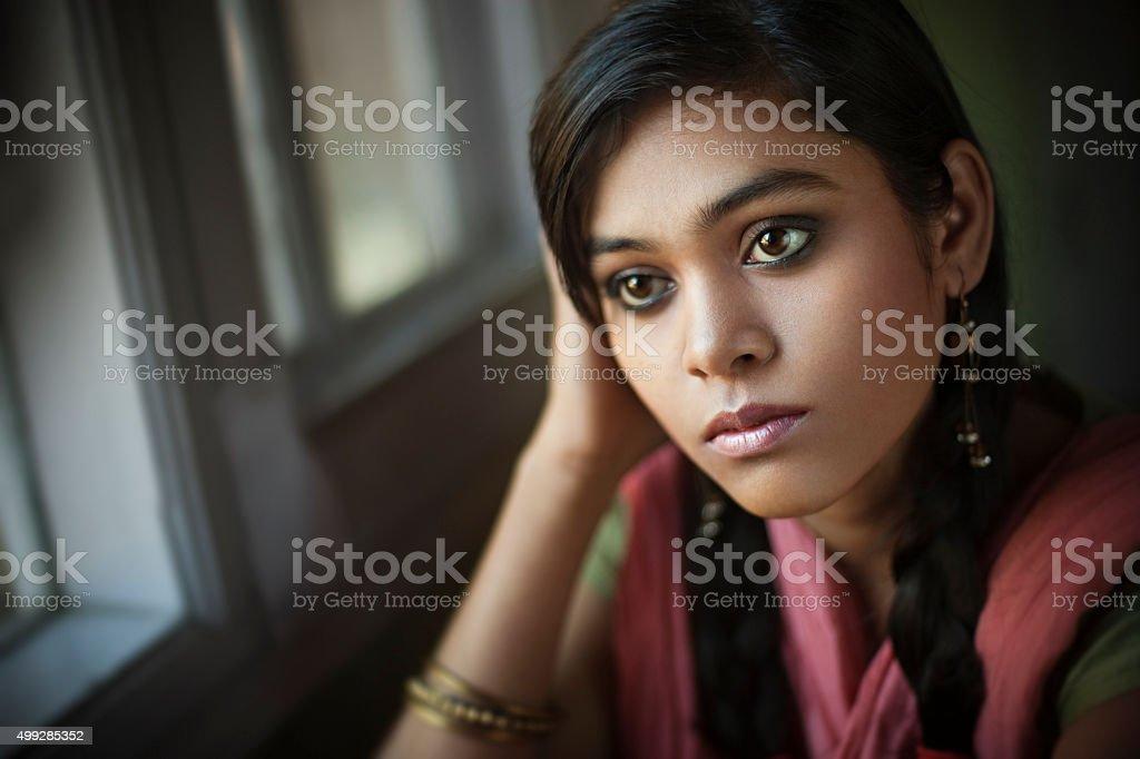Indoor close-up of serene Asian teenager girl sitting near window. stock photo