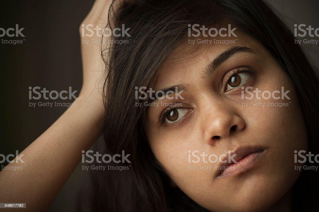 Indoor close-up of serene Asian teenager girl thinking. stock photo