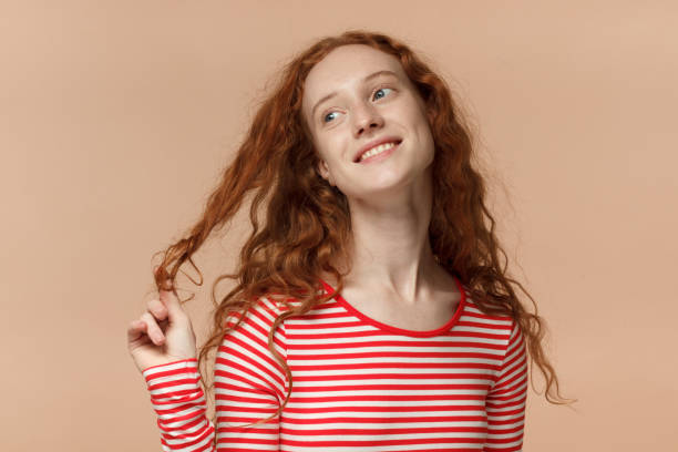 indoor closeup of young redhead european female pictured isolated on peach background dressed in striped t-shirt twisting her lock in fingers, looking upwards and aside while dreaming and smiling - puxar cabelos imagens e fotografias de stock