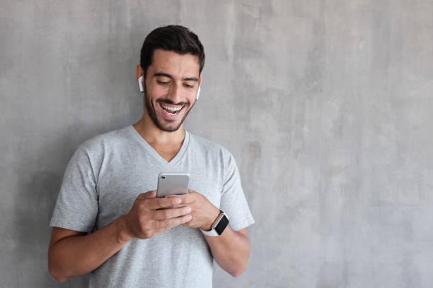 photo d'éclairage intérieur de jour de bel homme portant des t-shirt casual gris, rire heureusement être amusé de contenu sur l'écran du smartphone, qu'il tient à deux mains, debout contre le mur texturé - écouteurs intra auriculaires photos et images de collection