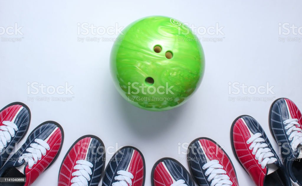 Indoor family sports. Many bowling shoes and bowling ball on white...