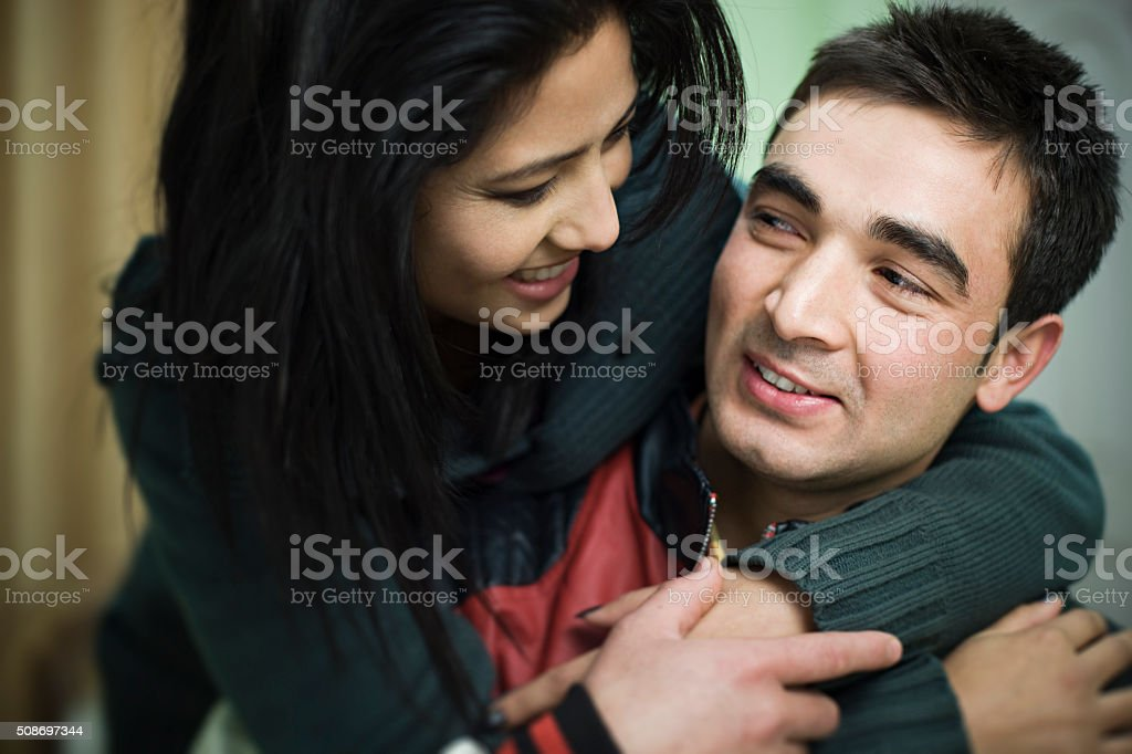 Indoor, happy and loving young couple holding each other. stock photo