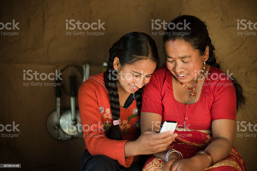 Indoor image of Asian daughter and mother sharing mobile phone. stock photo