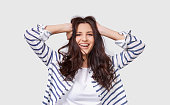 istock Indoor image of beautiful brunette young woman with long hair smiling cheerfully. Charming female smile broadly showing her white healthy teeth to camera while feeling happy and carefree. People 1153671226