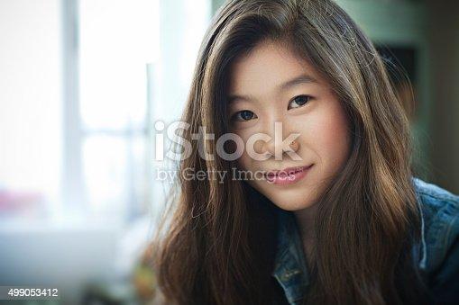 istock Indoor image of beautiful happy Asian girl looking at camera. 499053412