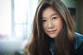 Day time indoor image of beautiful, happy late teen girl or young woman with long brown hair of Asian ethnicity looking at camera. Hade and shoulders, horizontal image with copy space and selective focus.