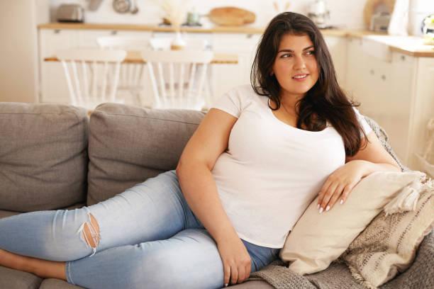 スタイリッシュなリッピングジーンズと白いtシャツを着たかわいい若いブルネットの女性の屋内イメージは、グレーのソファに快適に横たわって、幸せな笑顔でカメラを見て、アパートを掃 - real bodies ストックフォトと画像
