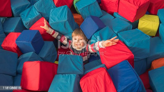 544818734 istock photo Indoor leisure activities, sports, recreation. Fun for preschoolers. Boy with arms raised up in mid-air. Welcome gesture. 1181086515