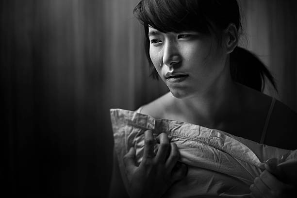 Indoor lonely teenage Asian girl crying with tears holding pillow. Indoor monochrome, black and white, low key image shot by using single light of a lonely cute teenage Asian girl crying with tears by holding and pressing a plane white pillow with her chest and looking away. Horizontal composition with copy space and selective focus. spaghetti straps stock pictures, royalty-free photos & images