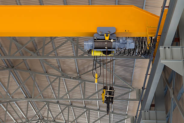 Indoor overhead crane on yellow steel beam with hanging block stock photo