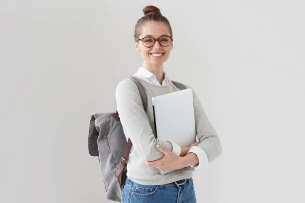 indoor photo of college student girl isolated on gray background, smiling at camera, pressing laptop to chest, wearing backpack, ready to go to studies, start new project and suggest new ideas. - studente foto e immagini stock
