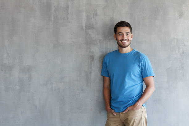 Indoor photo of handsome European guy pictured isolated against grey textured wall standing in blue T-shirt and trousers leaning to wall with shoulder, feeling confident and happy, enjoying free time stock photo