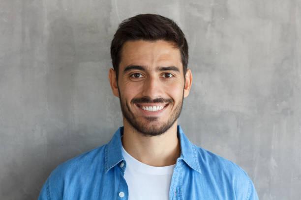 在灰色背景下的英俊的歐洲傢伙的室內照片站在靠近相機與深色的臉毛和短髮, 看起來滿意和快樂, 花他的閒暇時間 - 面部相 個照片及圖片檔