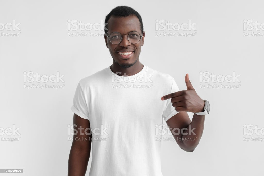 Indoor photo of young African American man pictured isolated on grey background pointing to his white blank T-shirt drawing attention to advertisement on it, promoting goods, apps or services stock photo