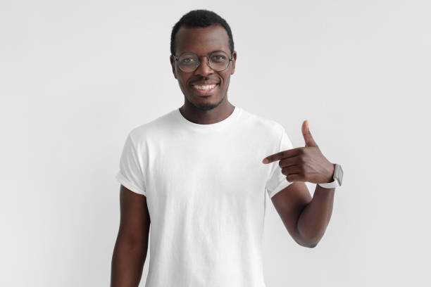 indoor photo of young african american man pictured isolated on grey background pointing to his white blank t-shirt drawing attention to advertisement on it, promoting goods, apps or services - t shirt stock photos and pictures