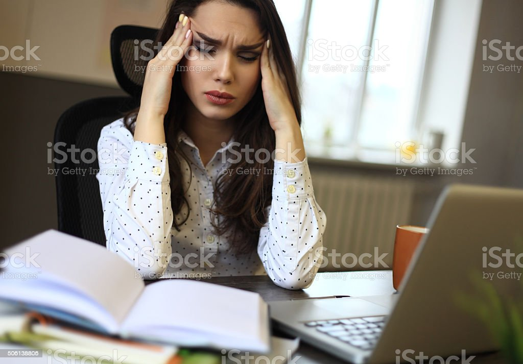 indoor picture of bored and tired woman taking notes stock photo
