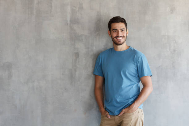 Indoor picture of handsome Caucasian guy pictured isolated on gray background posing against gray textured wall, smiling happily, copyspace on left for promoting products for electronic commerce Indoor picture of handsome Caucasian guy pictured isolated on gray background posing against gray textured wall, smiling happily, copyspace on left for promoting products for electronic commerce male likeness stock pictures, royalty-free photos & images