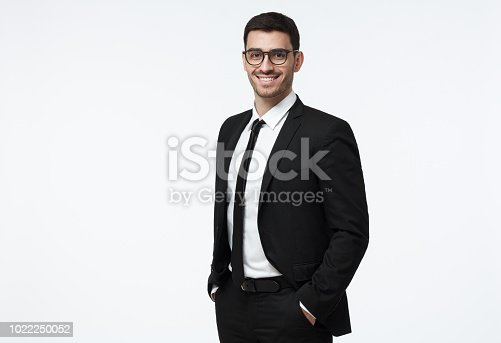 istock Indoor picture of young business man in glasses pictured isolated on grey background looking straight at camera, showing confidence and providing stability for employees 1022250052