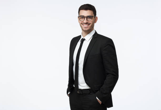 Indoor picture of young business man in glasses pictured isolated on grey background looking straight at camera, showing confidence and providing stability for employees Indoor picture of young business man in glasses pictured isolated on grey background looking straight at camera, showing confidence and providing stability for employees male likeness stock pictures, royalty-free photos & images