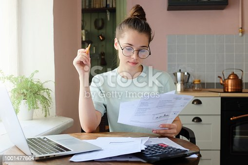 istock Indoor picture of young European female sitting at home at table 1001477664