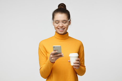 Indoor picture of young good-looking European woman isolated on gray background holding phone in hand, looking to screen smiling while browsing or reading message