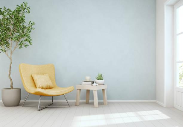 indoor-anlage und einen couchtisch auf holzboden mit leeren blauen betonwand hintergrund, gelber stuhl neben der tür in hellen wohnzimmer modernen skandinavischen hauses - betonboden wohnzimmer stock-fotos und bilder