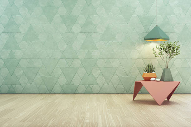 Indoor plant on pink steel coffee table and lamp with empty turquoise triangle pattern wall background, Relaxing area in pastel room of modern house. - foto stock