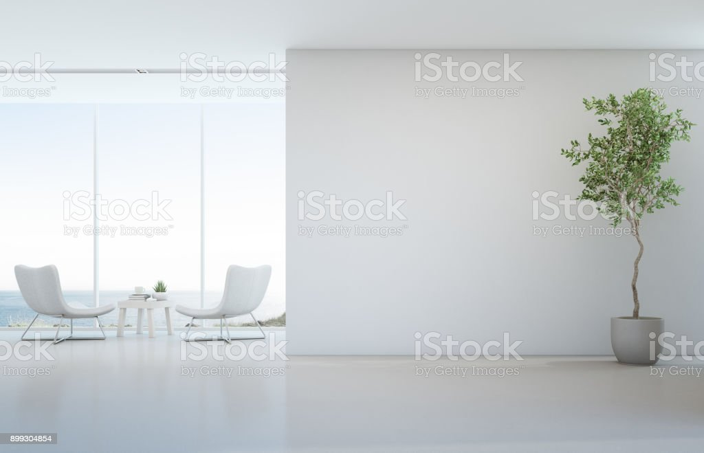 Indoor plant on white floor with empty concrete wall background, Lounge and coffee table near glass window in sea view living room of modern luxury beach house or hotel