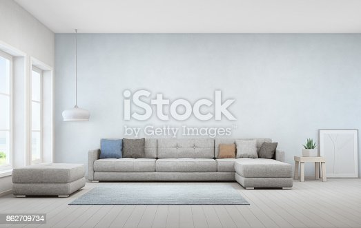 istock Indoor plant on wooden coffee table and big sofa with empty blue concrete wall background, Relaxing area near window in sea view living room of modern luxury beach house 862709734