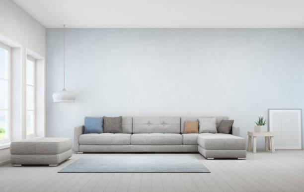 indoor-anlage am couchtisch aus holz und großes sofa mit leeren blauen betonwand hintergrund, entspannende nähe fenster im wohn-zimmer mit meerblick des modernen luxus-strandhaus - große wohnzimmer stock-fotos und bilder