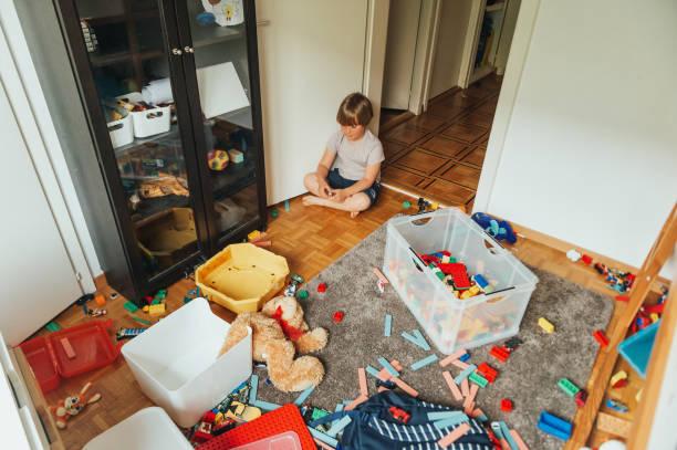 Innenporträt eines Kindes, das in einem sehr chaotischen Raum spielt – Foto