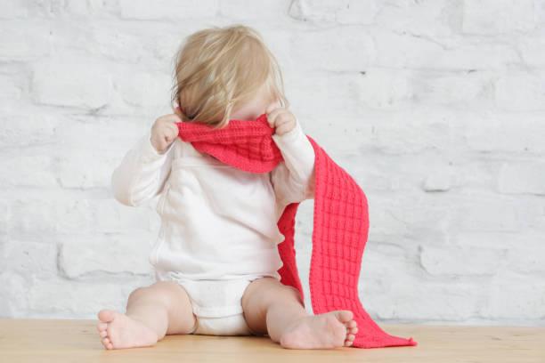 Indoor-Porträt von einer netten Blondine baby tragen einen roten Wolle Schal, ein Kuckuck Spiel oder nicht wollen, verkleiden sich Konzept – Foto