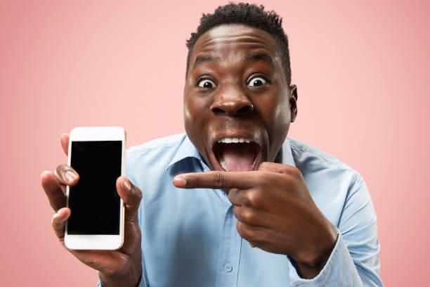 indoor-porträt von attraktiven junger schwarzer mann hält leere smartphone - die besten apps stock-fotos und bilder