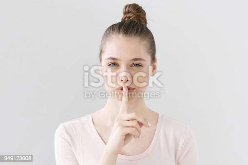 Indoor portrait of beautiful European female isolated on gray background pressing forefinger to lips to make interlocutor silent, smiling intricately with secrecy as if promising something exciting.